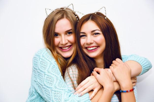 一緒に楽しんでいるかわいい姉妹のかわいいファッションポートレート抱擁し、夢中になる、面白い猫の耳、ミントの冬のセーター、白い壁、親友、喜び、トレンド、関係、幸せ、自然なメイクアップ。 無料写真
