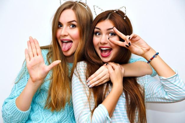 Симпатичный модный портрет красивых женщин-сестер, веселящихся вместе, объятий и сходящих с ума, забавные кошачьи уши, мятные зимние свитера, белая стена, лучшие друзья, радость, тренд, отношения, счастливый, естественный макияж. Бесплатные Фотографии