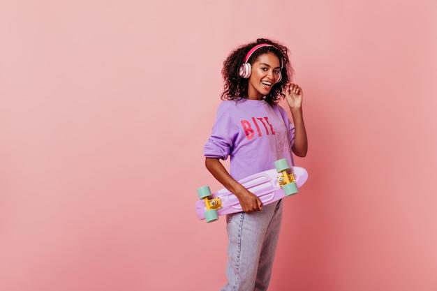 보라색 스케이트 보드를 들고 귀여운 여성 블랙 모델입니다. 곱슬 헤어 스타일 좋아하는 노래를 듣고 웃 고 사랑스러운 아프리카 여자. 무료 사진