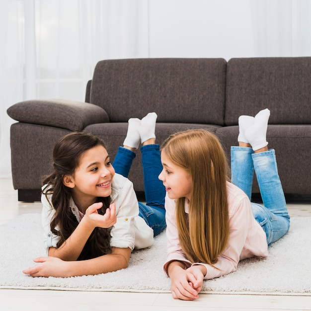 Cute female friends lying on carpet talking to each other Free Photo