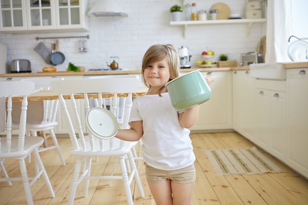 Cute female kid in casual clothes holding casserole and holder, having excited look, going to cook soup, modern kitchen Free Photo