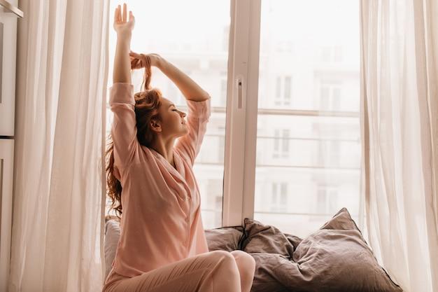 Милая женская модель в розовой пижаме, наслаждаясь утром. приятная имбирь женщина, сидящая на кровати. Бесплатные Фотографии