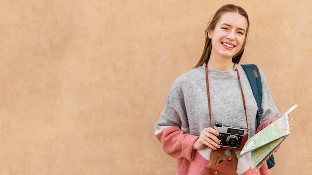 地図とカメラのコピースペースを保持しているかわいい女性観光客 無料写真