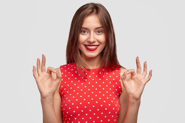 Симпатичная девушка с очаровательной дружелюбной улыбкой, хорошо жестикулирует, одетая в модное платье в горошек, демонстрирует одобрение, позирует у белой стены. молодая женщина с красными губами моделирует крытые. Бесплатные Фотографии