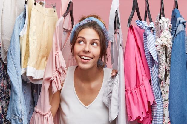 ハンガーに洋服を着て、おしゃれなドレスやブラウスを夢見て夢のような表情のかわいい女性。週末に友達と買い物に行くことについて空想にふける愛らしい女性 無料写真