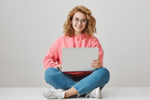 Симпатичная девушка-фрилансер с помощью ноутбука, сидя на полу и улыбаясь Бесплатные Фотографии