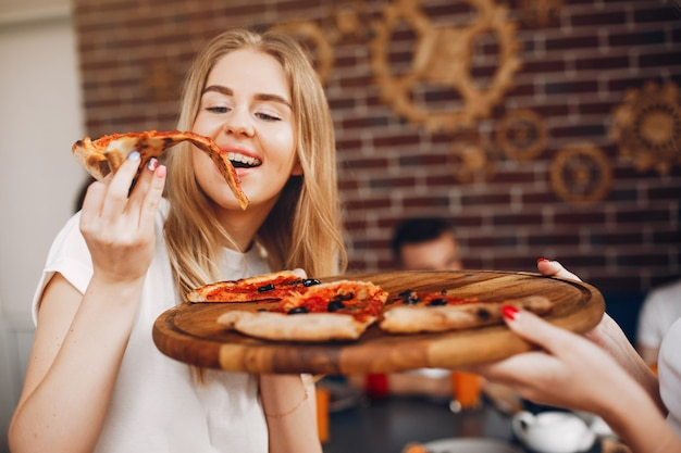 ピザを食べてカフェでかわいい友達 無料写真