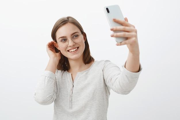 本当の愛を待っている出会い系アプリで送信するselfieを作るかわいい穏やかな女性が耳の後ろに髪の束をフリックして、灰色の壁に女性の立っているスマートフォンの画面で優しく微笑んでくる 無料写真