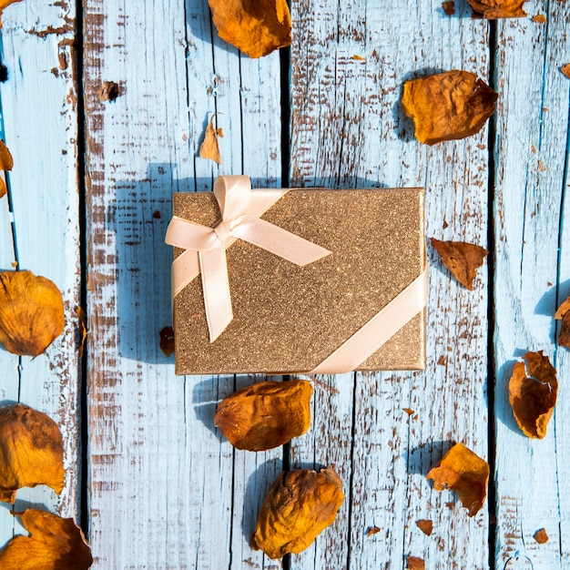 Cute gift surrounded by dried leaves Free Photo