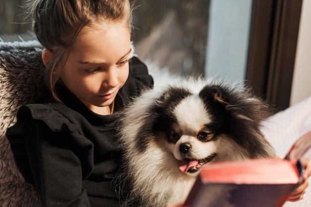Милая девочка и собака, читающая Бесплатные Фотографии