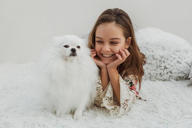 かわいい女の子と犬のベッドに座って 無料写真