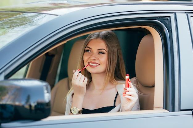 車の中で口紅を塗るかわいい女の子 無料写真