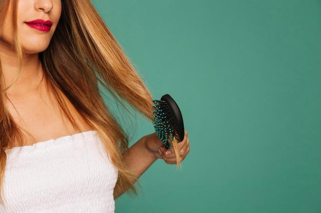 Cute girl brushing her hair Free Photo