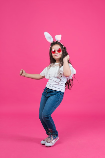 Cute girl in bunny ears dancing Premium Photo
