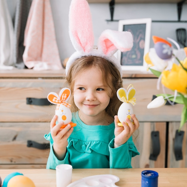 Cute girl in bunny ears holding easter eggs Free Photo