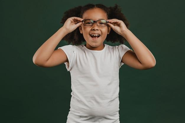 Cute girl child arranging her glasses Premium Photo