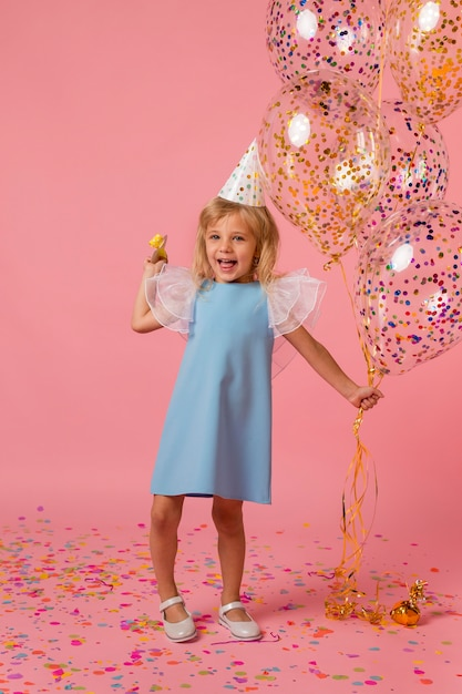 Ragazza carina in costume con palloncini e cappello da festa Foto Gratuite