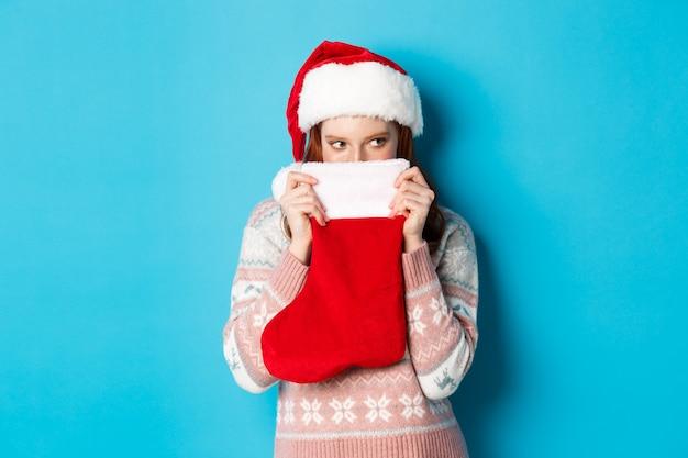 かわいい女の子は、クリスマスの靴下で顔を覆い、狡猾な視線で右を見つめ、サンタの帽子に立って、冬の休日を祝う、青い背景。 Premium写真