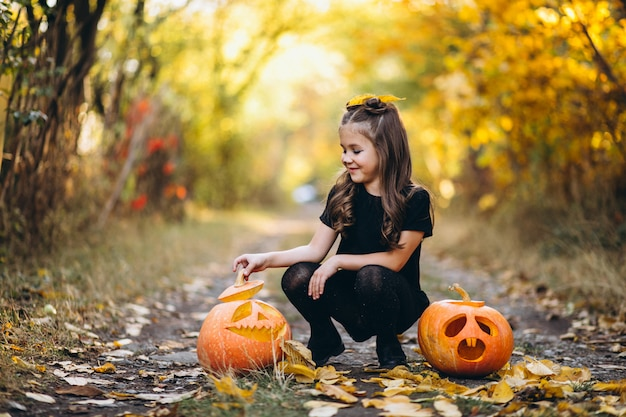 Cute girl dressed in halloween costume outdoors with pumpkins Free Photo