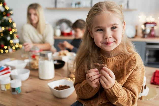 Ragazza carina che mangia biscotti fatti in casa mentre è seduto sul tavolo Foto Gratuite