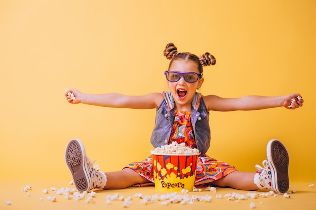 Cute girl eating popcorn Free Photo