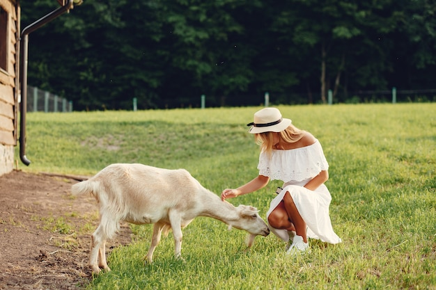 Cute girl in a field with a goats Free Photo