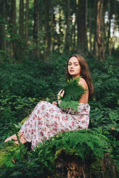 A cute girl in a floral dress is sitting with a fern bouquet in the forest. Premium Photo
