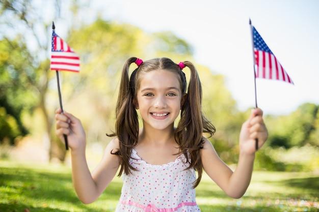 Cute girl holding american flags Premium Photo