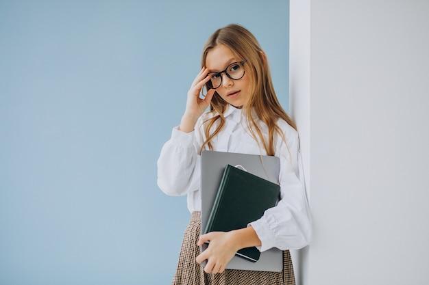 Ragazza sveglia che tiene libro e laptop in ufficio Foto Gratuite