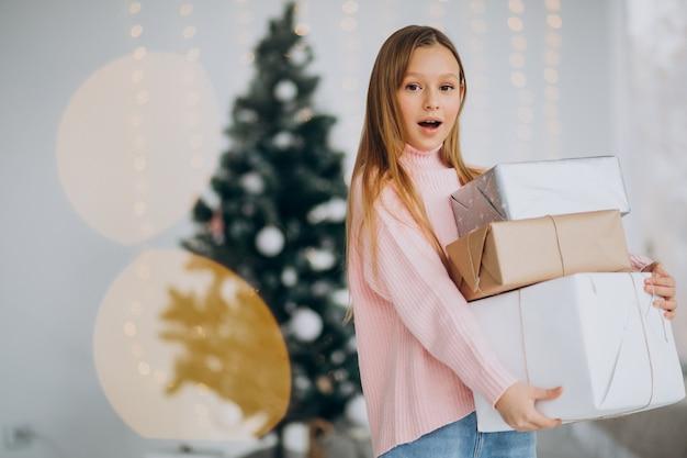 クリスマスツリーでクリスマスプレゼントを持っているかわいい女の子 無料写真