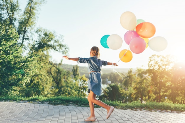 Cute girl holding colorful balloons in the city park Free Photo