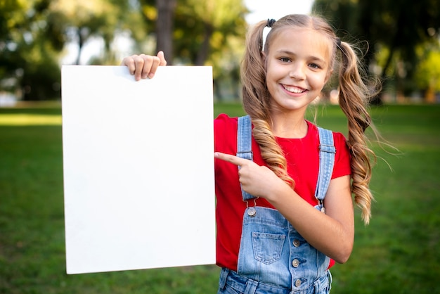 Cute girl holding empty banner in her hand Free Photo