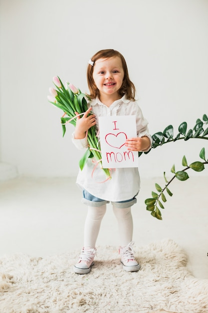 Cute girl holding greeting card with i love mom inscription Free Photo