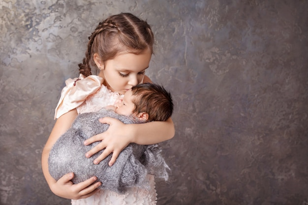 Cute girl holding her little brother. happy sister kissing her newborn baby brother. copyspace Premium Photo