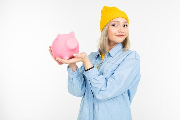 Милая девушка в синей рубашке с банком для экономии денег на белом фоне с копией пространства Premium Фотографии