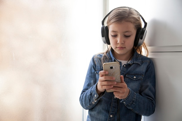 Cute girl in headphones using smartphone Free Photo
