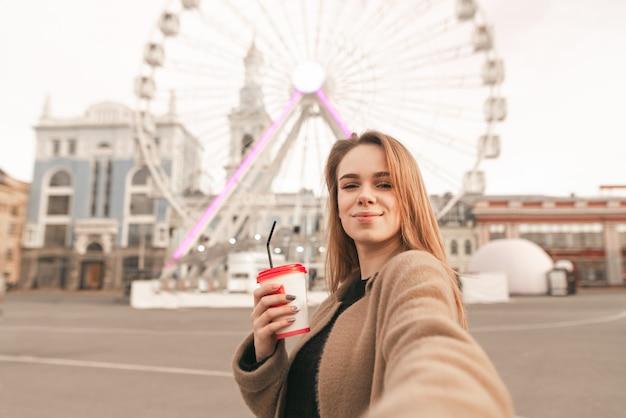 Симпатичная девушка в весенней одежде, в пальто, держит чашку кофе в руке и делает селфи на фоне улицы Premium Фотографии
