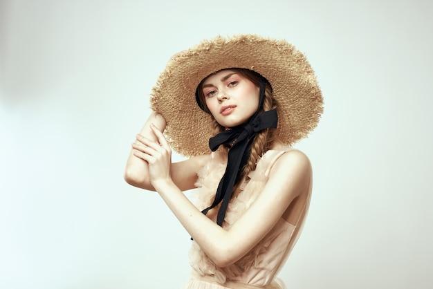 Милая девушка в соломенной шляпе с черной лентой и платье на светлом фоне обрезанный вид Premium Фотографии