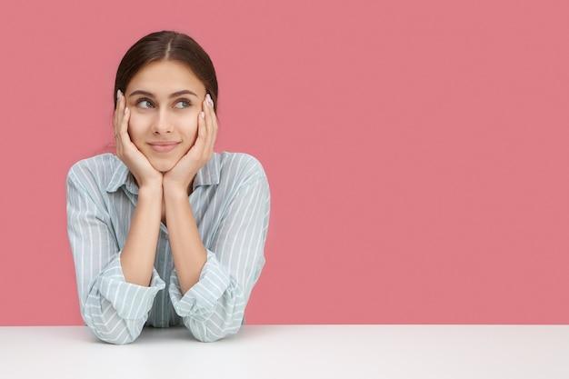 Милая девушка в стильной полосатой рубашке сидит на своем рабочем месте, опершись локтями о стол, подперев лицо руками, глядя в сторону со скучающим или задумчивым выражением лица, думая, как развлечь себя Бесплатные Фотографии