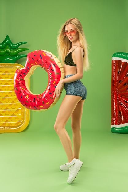 インフレータブル水泳サークルでスタジオでポーズをとる水着のかわいい女の子。緑の夏の肖像画白人ティーンエイジャー 無料写真