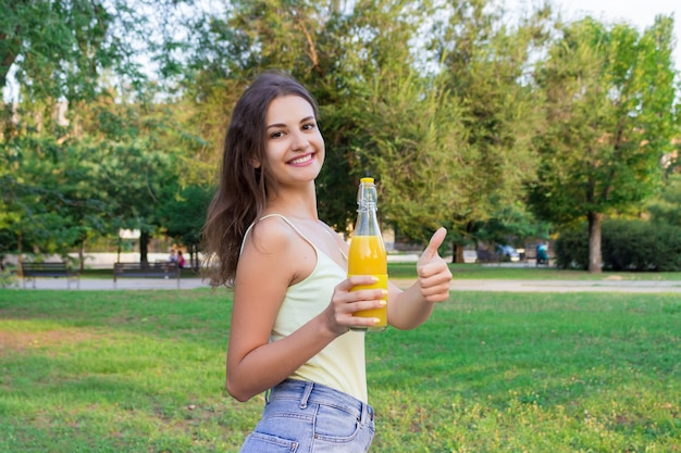 Cute girl is having a walk in the park holding a bottle of orange juice in a sunny wam day Premium Photo