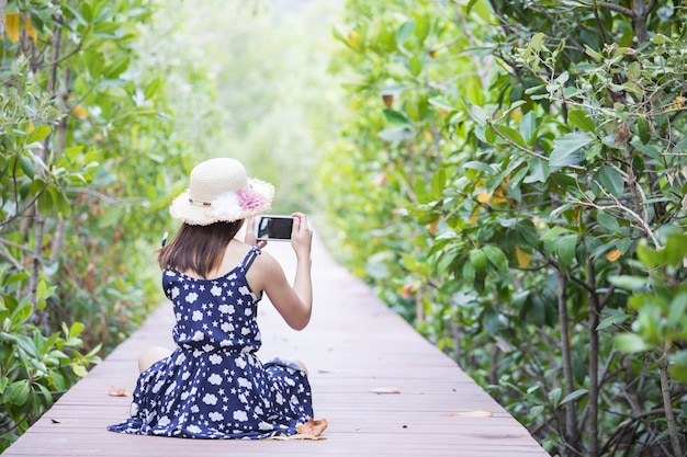 Cute girl is traveling on wooden -walkway in mangrove forest. Premium Photo