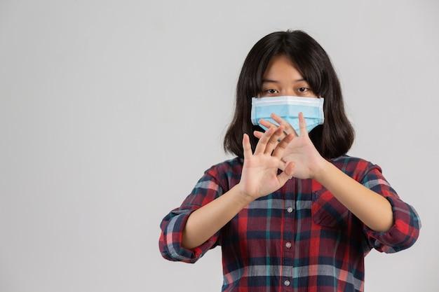 かわいい女の子はマスクをしていて、白い壁に他のプロパティからストップハンドを作っています。 無料写真