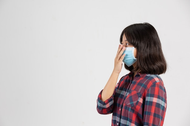 Cute girl is wearing mask and putting her hand up while close mouth by hand on white wall. Free Photo