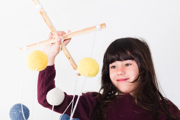 Cute girl manipulating marionette Free Photo