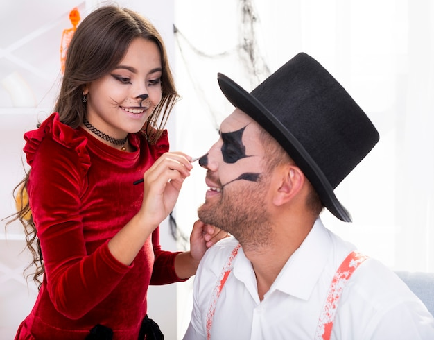 Cute girl painting fathers face for halloween Free Photo