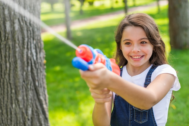 Cute Girl Playing With A Water Gun Free Photo