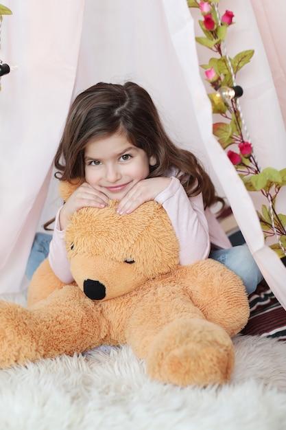 Ragazza carina in posa con il grande orsacchiotto Foto Gratuite