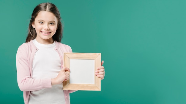 Cute girlposing with photo frame in studio Free Photo