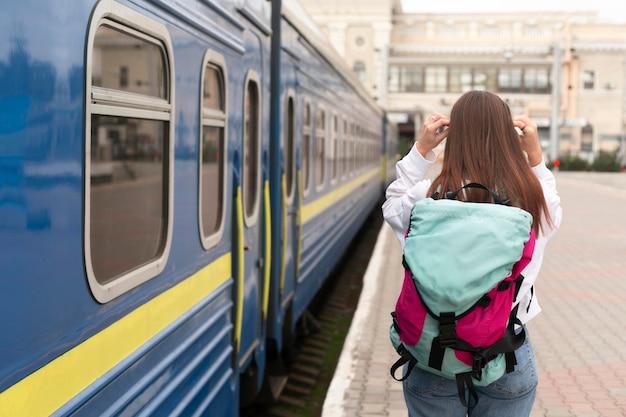 Ragazza carina alla stazione ferroviaria da dietro il colpo Foto Gratuite